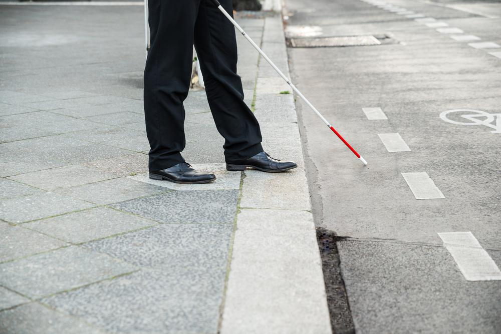 Low Section Of A Blind Person Crossing Street